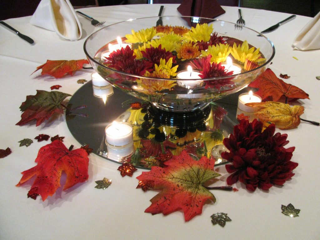 Glass centerpiece with and floating flowers and candles
