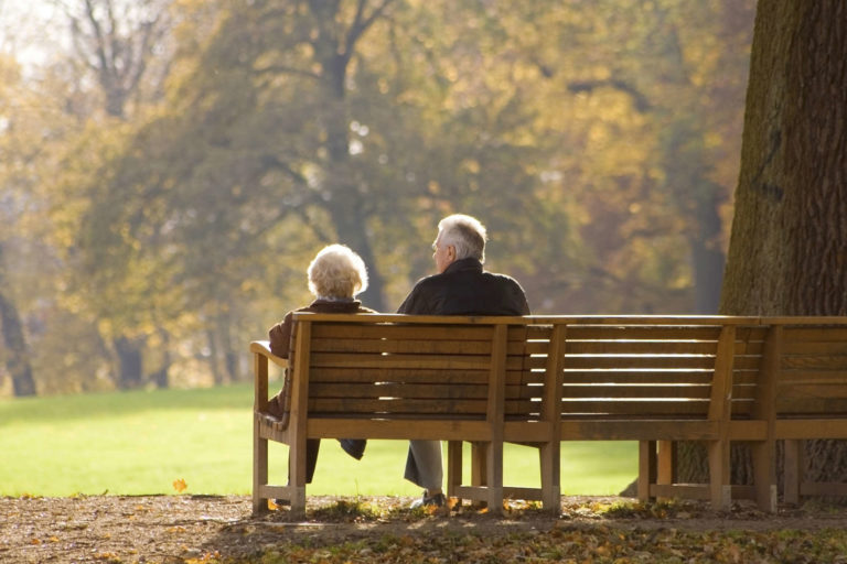 Picturesque couple sitting on a park bench in the middle of fall | Thanksgiving.com