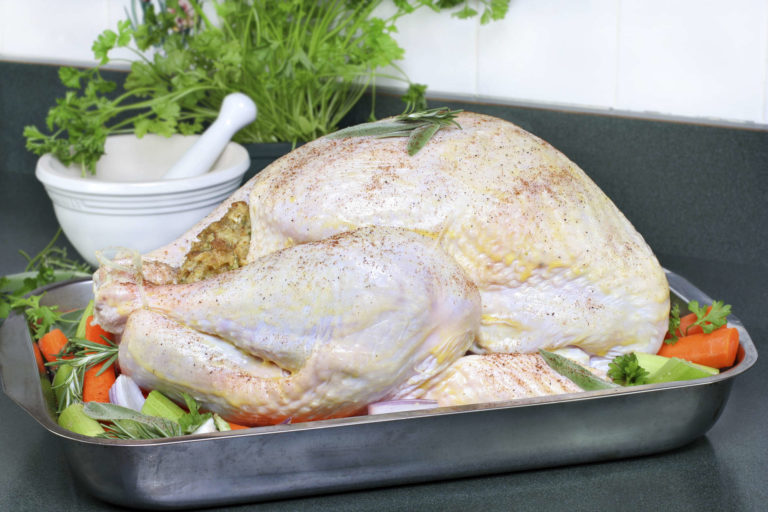 Whole raw turkey, dressed with butter, spices and surrounded with veggies - oven ready   Thanksgiving.com