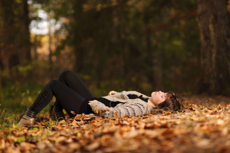 Peaceful moment as a woman sleeps in the middle of a pile of leaves   Thanksgiving.com