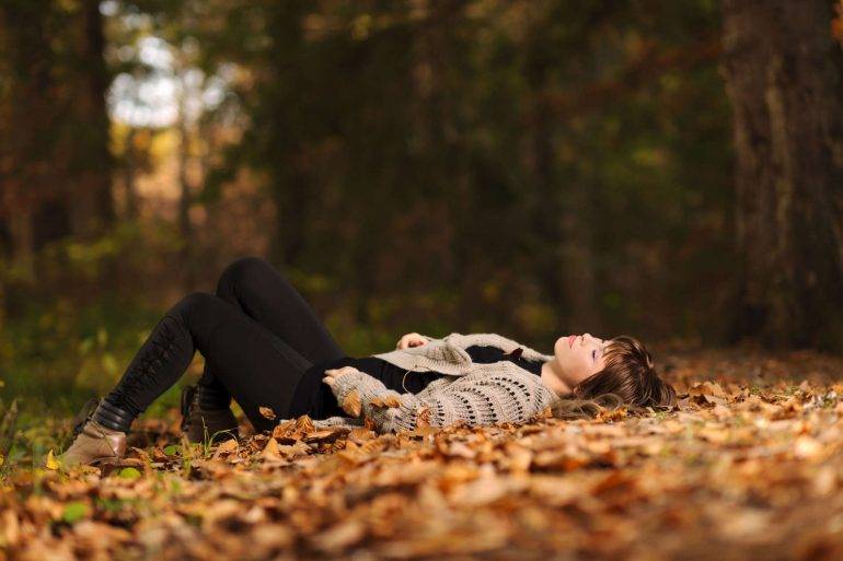 Peaceful moment as a woman sleeps in the middle of a pile of leaves | Thanksgiving.com