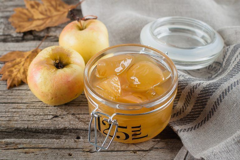 Homemade apple jam or sauce in jar on table. Wooden rustic background, close up
