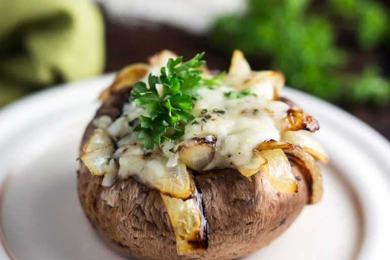 These sweet and savory Caramelized Onion and Spinach Stuffed Mushrooms topped with melted cheese are the perfect rich and flavorful Thanksgiving starter | Thanksgiving.com