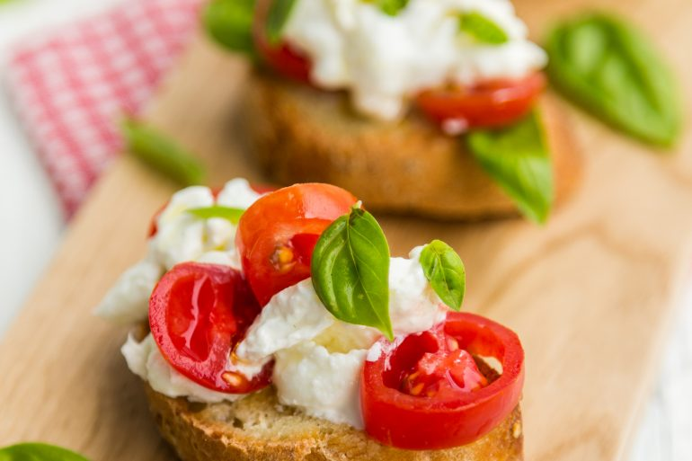 Crostini with soft cheese, fresh tomatoes and basil