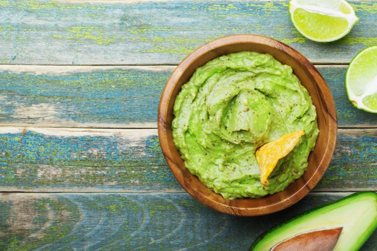 Green guacamole with ingredients avocado, lime and nachos on wooden vintage table top view.