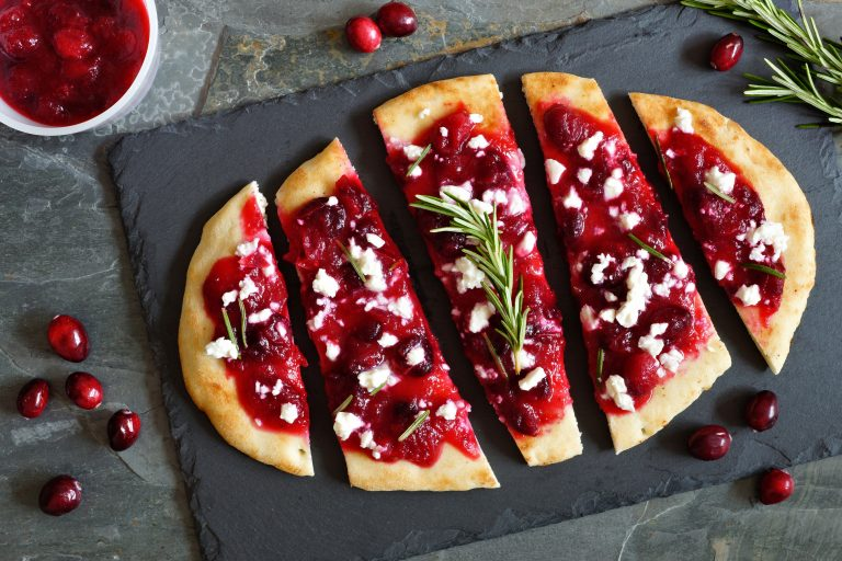 Holiday flatbread appetizer with cranberries and cheese, overhead scene