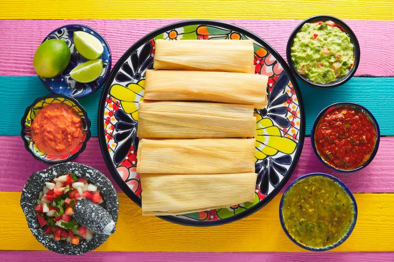 Tamale with corn leaf and sauces guacamole
