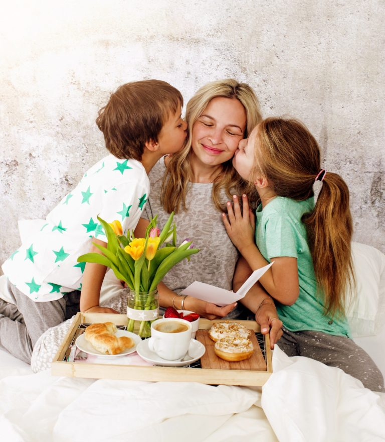 Mother´s Day - two children surprise their mother with breakfast in modern bed