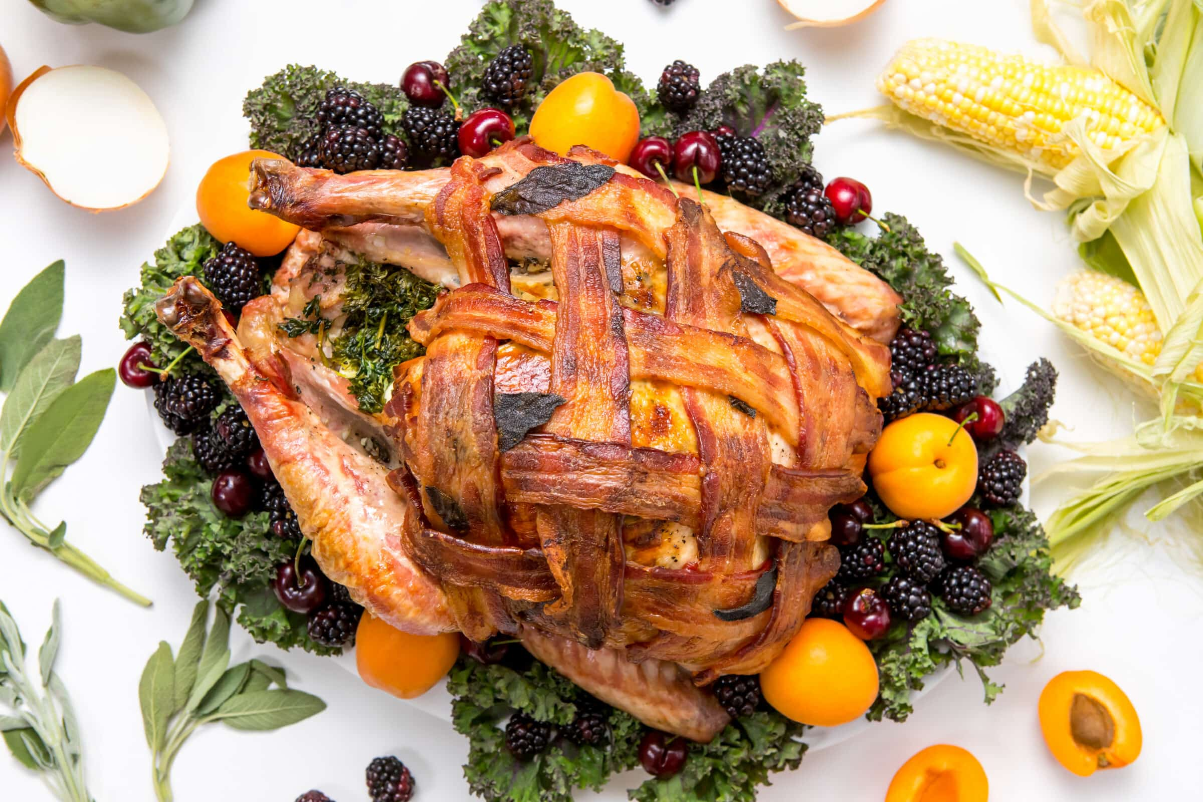 5D4B9754 - Bacon Wrapped Turkey - plated bacon wrapped turkey on a white table surrounded by corn, oranges, onions, bell pepper, blueberries, apricots and sage