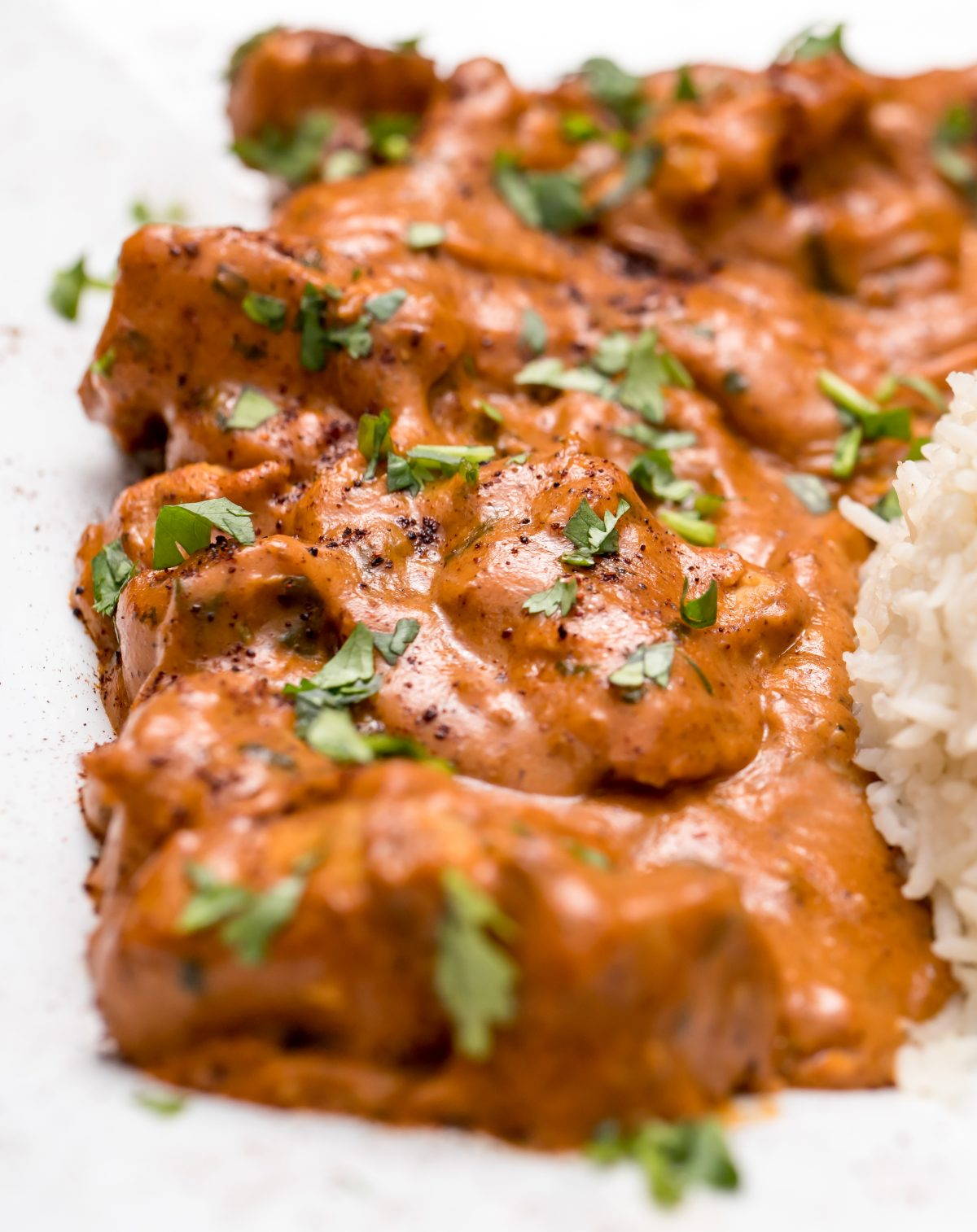 Instant Pot Butter Chicken - instant pot butter chicken on a white plate with white rice, and cilantro