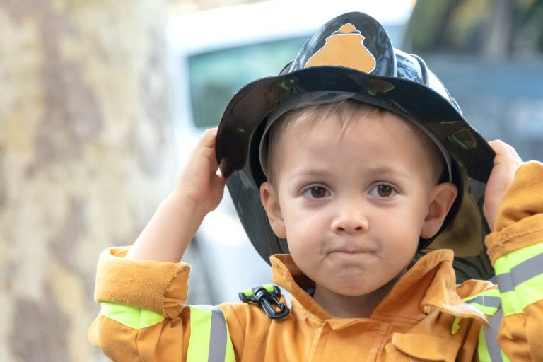 toddler posing wearing a firefighter costume