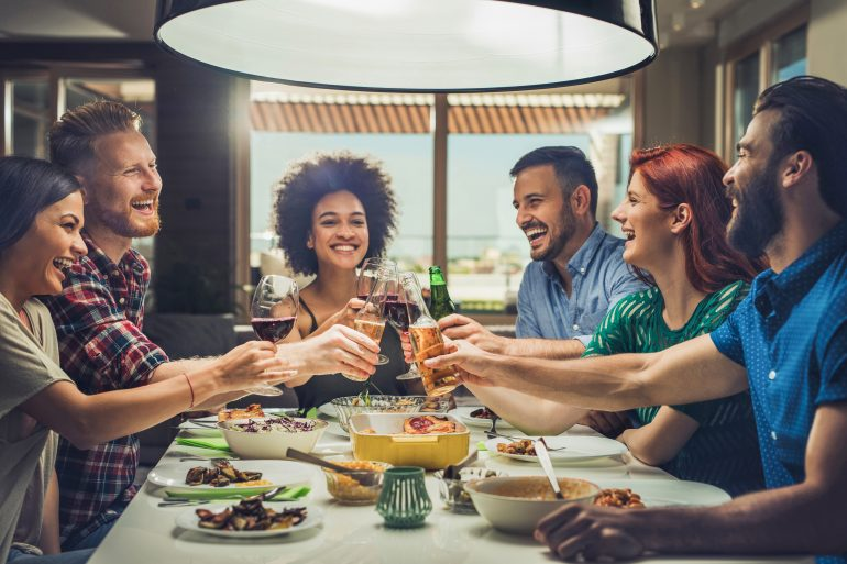 Group of happy friends toasting while eating at dining table.