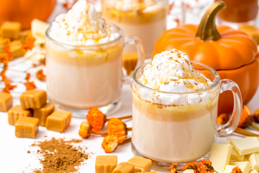 5D4B7327-Boozy-Pumpkin-Hot-Chocolate-served-hot-pumpkin-spice-on-a-white-table-surrounded-by-caramels-pumpkin-spice-and-pumpkins