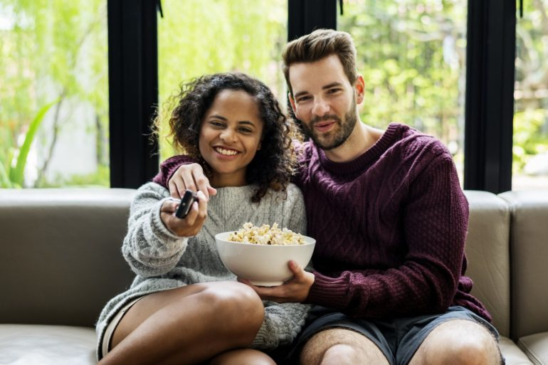 Couple watching TV having popcoprn