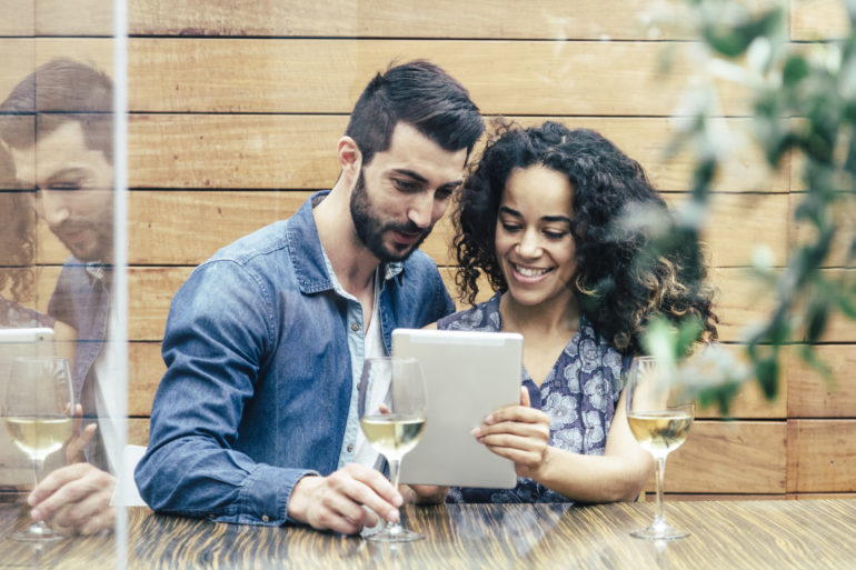 Multiethnic couple in a restaurant looking at tablet
