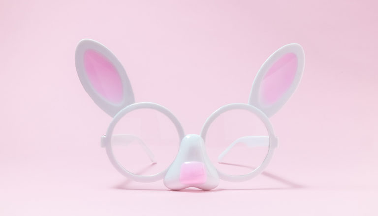 Eyeglasses in form of bunny face against pink rose pastel background minimalistic easter concept