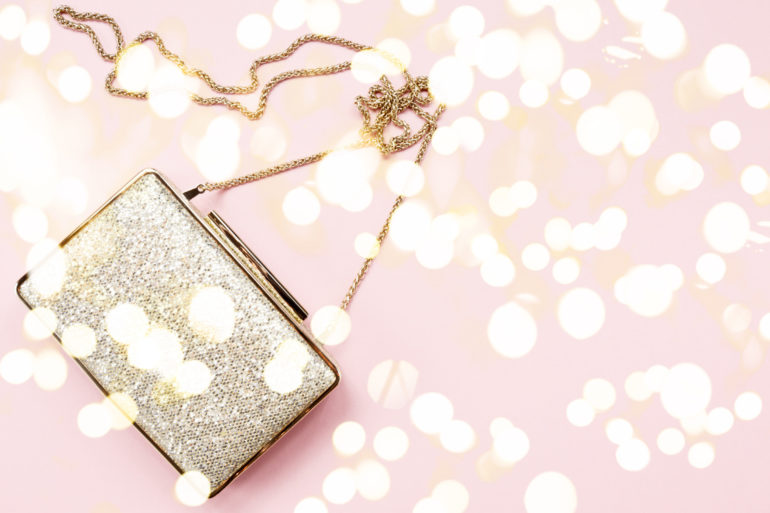 Festive evening golden clutch on pink. Holiday and celebration background. Luxury accessories and party concept