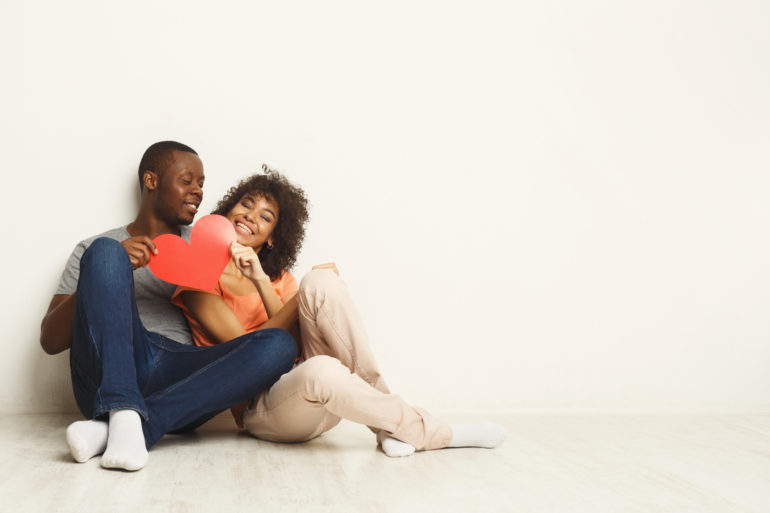 Happy african-american couple holding paper heart