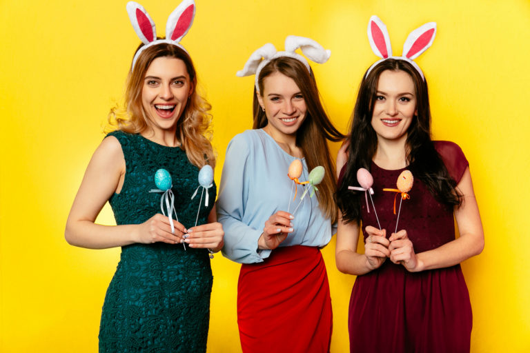 Charming women wearing bunny ears with easter eggs while posing at camera