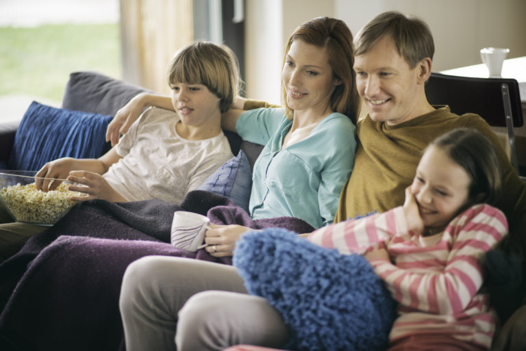 Family relaxing on sofa watching television