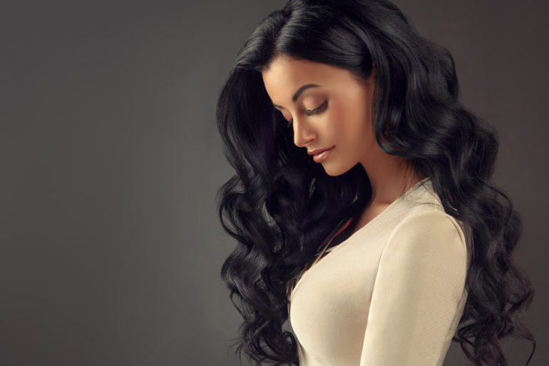 Black haired woman with voluminous, shiny and curly hairstyle.Frizzy hair.
