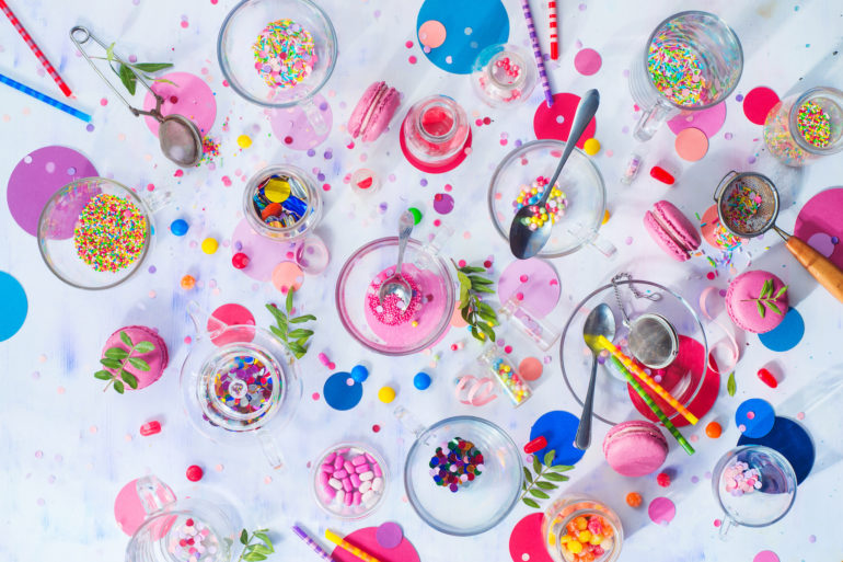 Party supplies in glass tea cups. Sprinkles, confetti, candies, macaroons and birthday candles on a white background. After party concept