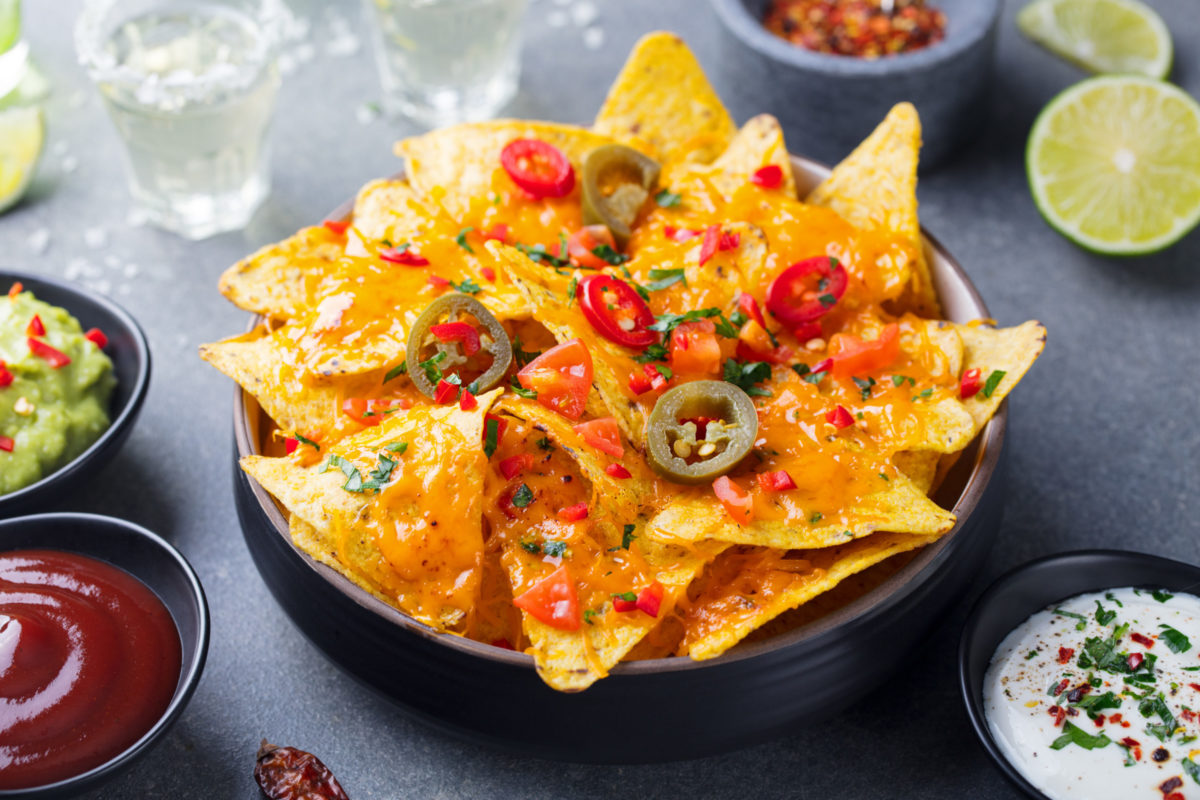 Nachos chips with melted cheese and dips variety in black bowl. Grey stone background