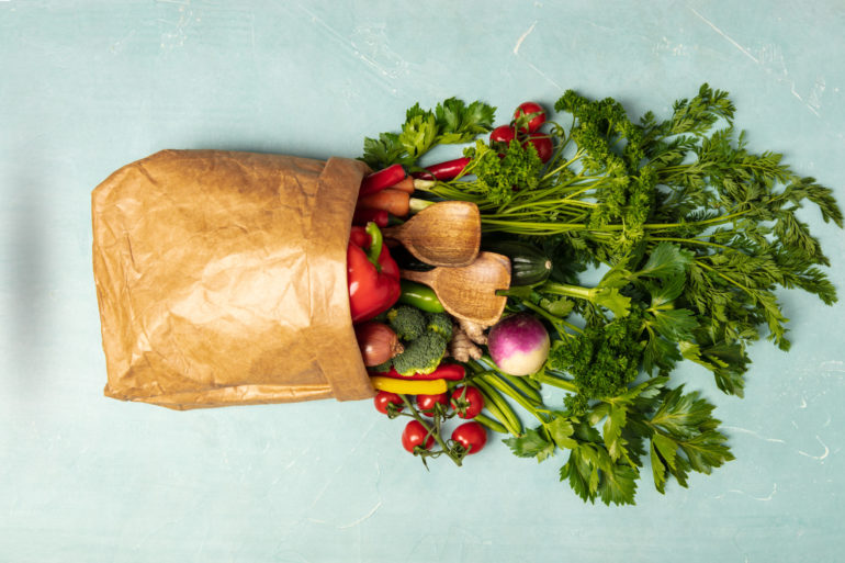 Grocery shopping concept. Different food in paper bag on colorful background