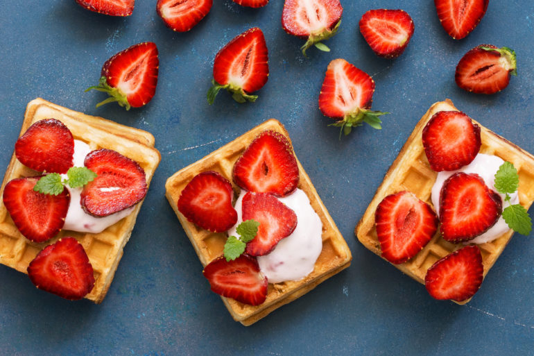 Homemade Belgian waffles with cream and fresh strawberries on a blue woody background. Top view, flat lay, space for text.