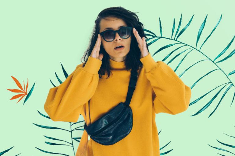 Beautiful woman in sunglasses, belt bag and sweatshirt.