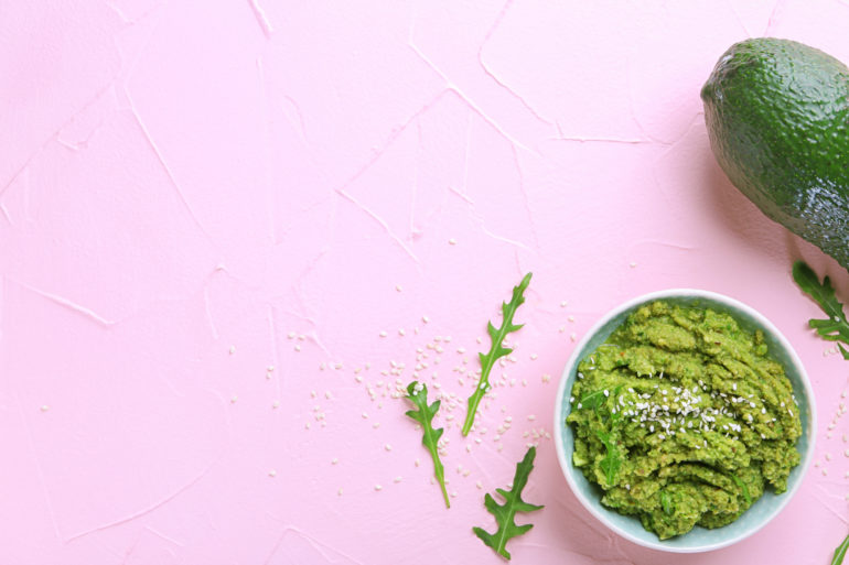 Bowl with tasty guacamole and ripe avocado on color background