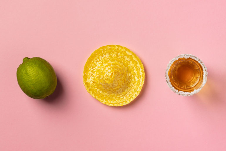 Sombrero, lime, tequila and cactus on pink background.
