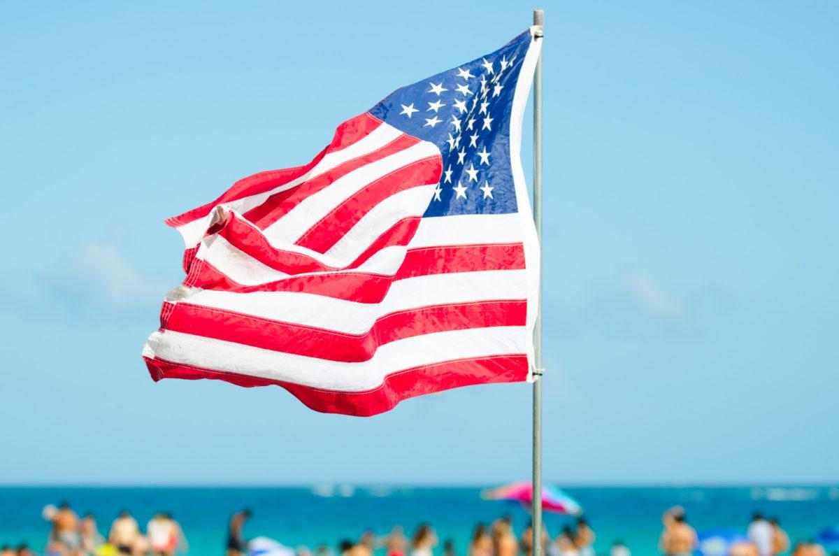 American Flag Flying Over Bright Beach Scene