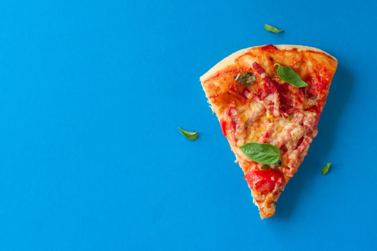 One piece of salami pizza on blue background. Top view and copy