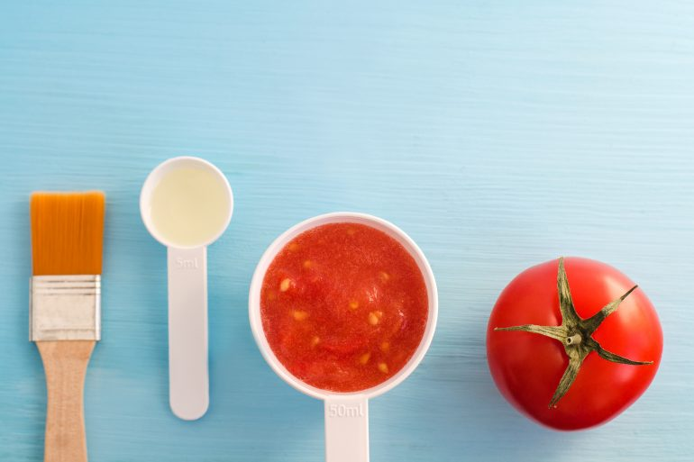 Plastic scoops with tomato puree and olive oil. Ingredients for preparing homemade facial mask. DIY cosmetics recipe. Top view, copy space.