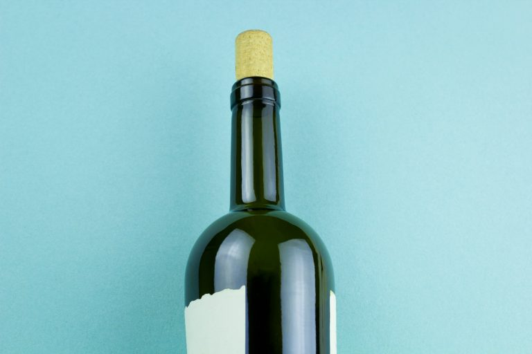 Bottle of wine with white label on blue background