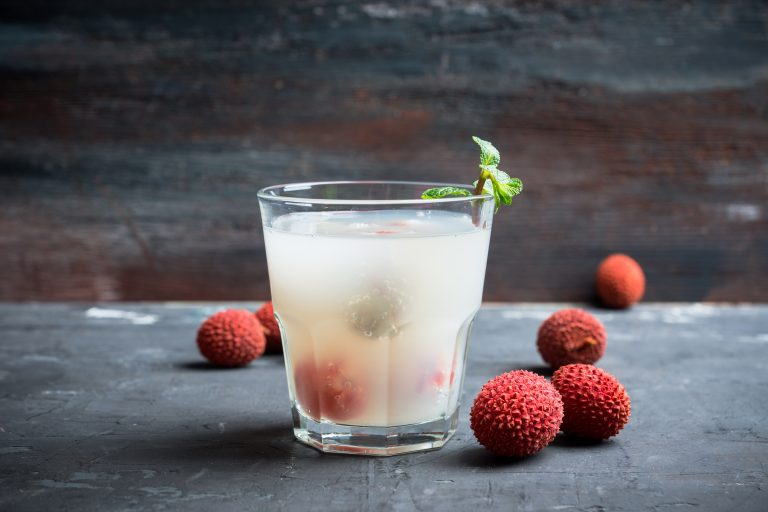 Old fahioned lychee cocktail on the rustic background